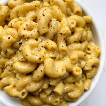 dairy free mac and cheese in bowl with black pepper