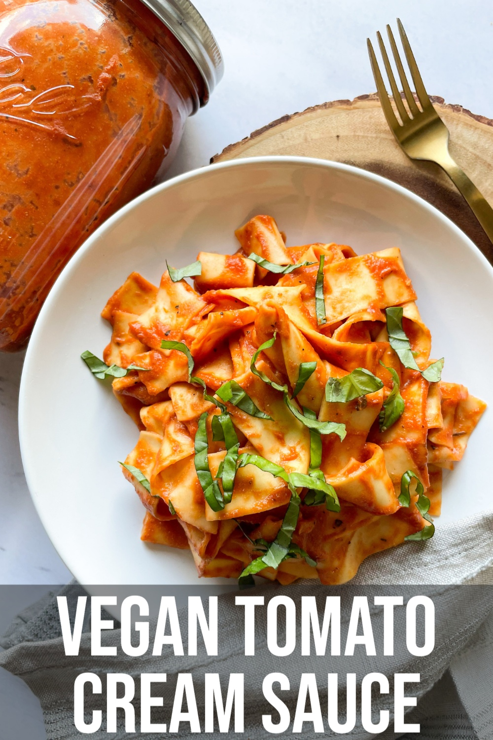 pasta with vegan tomato cream sauce on a white plate with text overlay