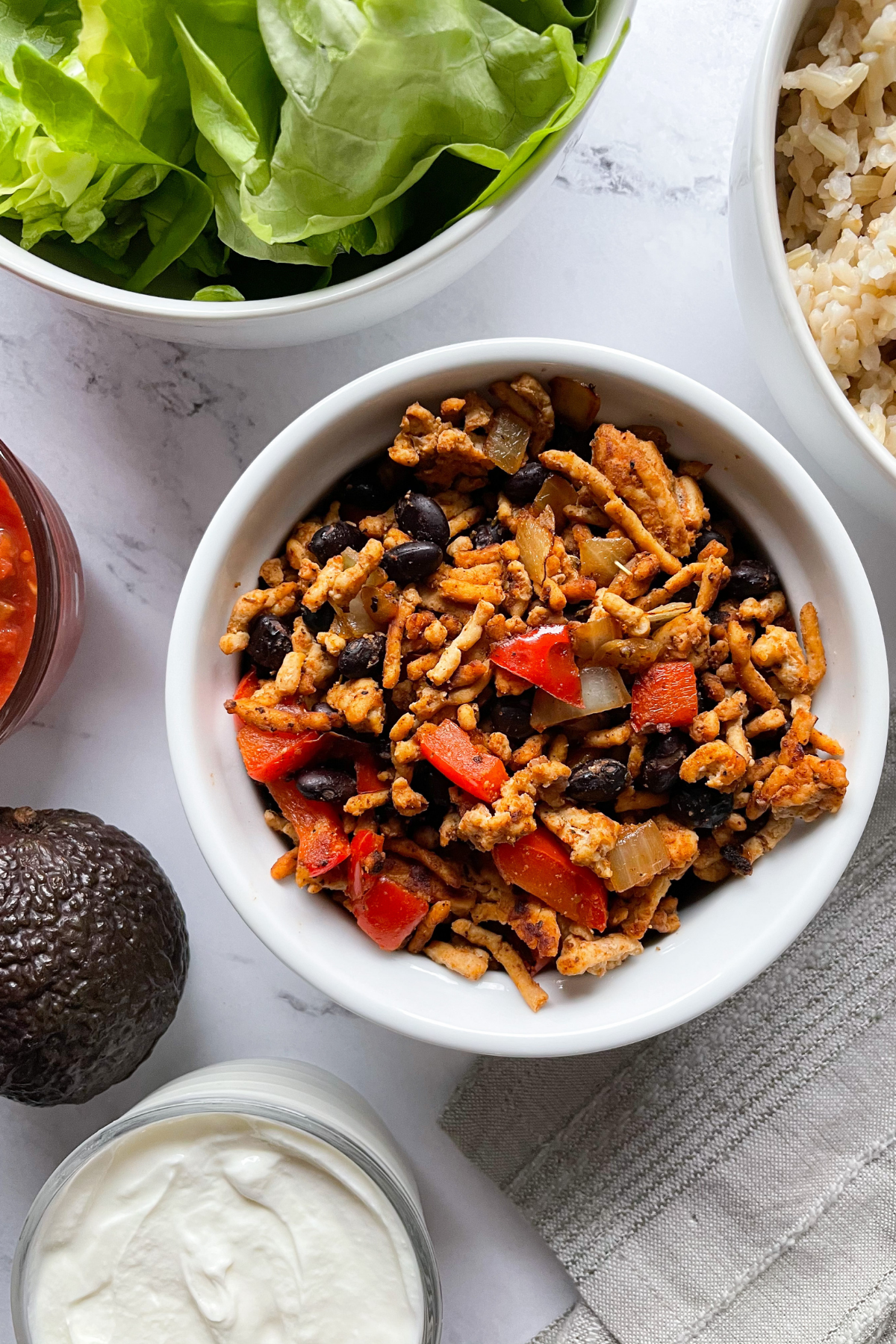 all ingredients in bowls for chicken burrito bowl recipe
