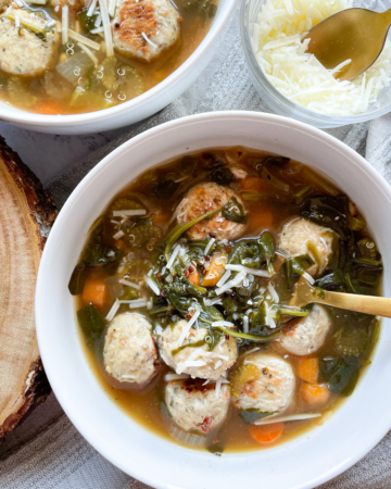Healthy Italian Wedding Soup in 2 White Bowls, Gold Spoons and Cheese
