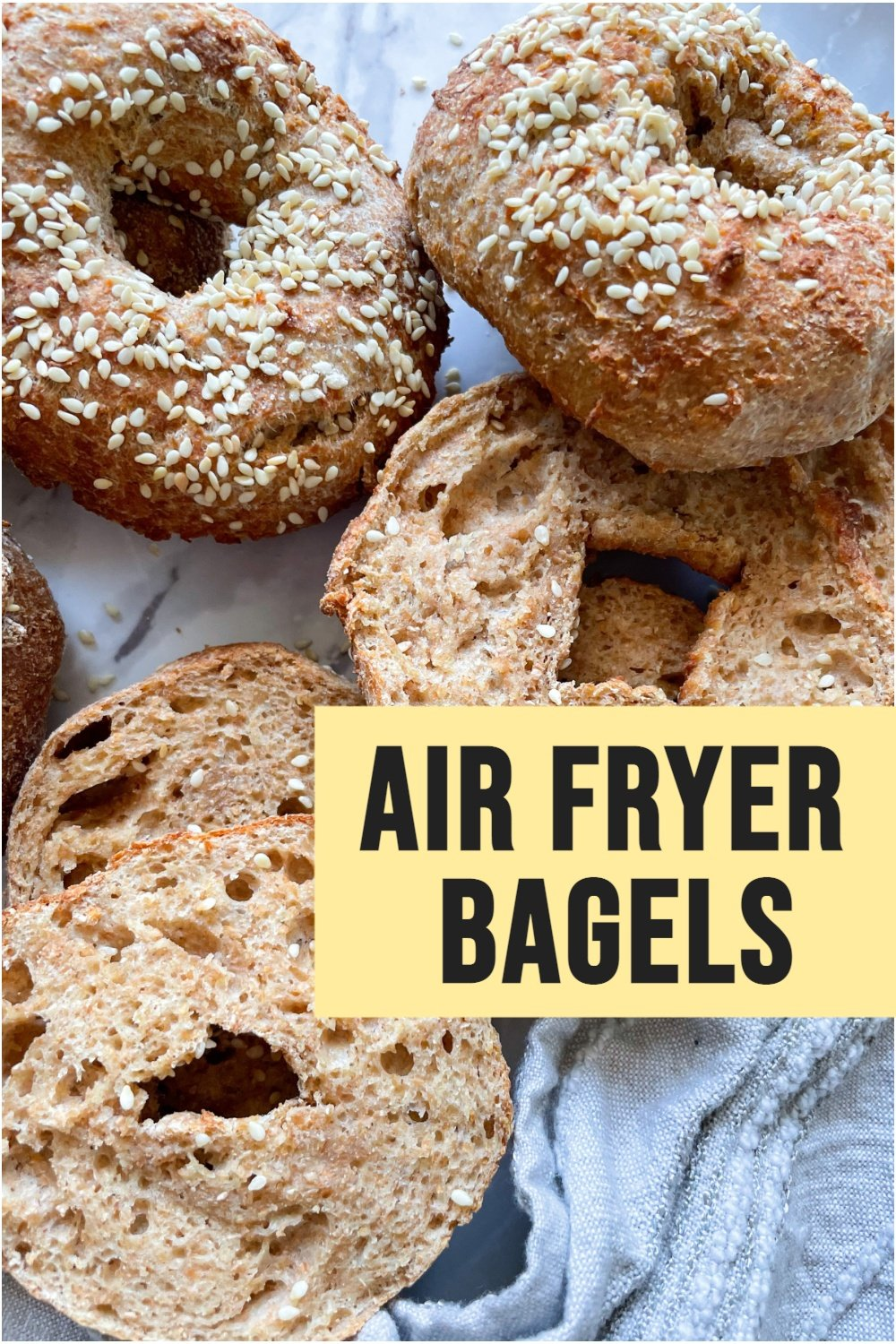 bagels on marble background and grey dish towel with text overlay