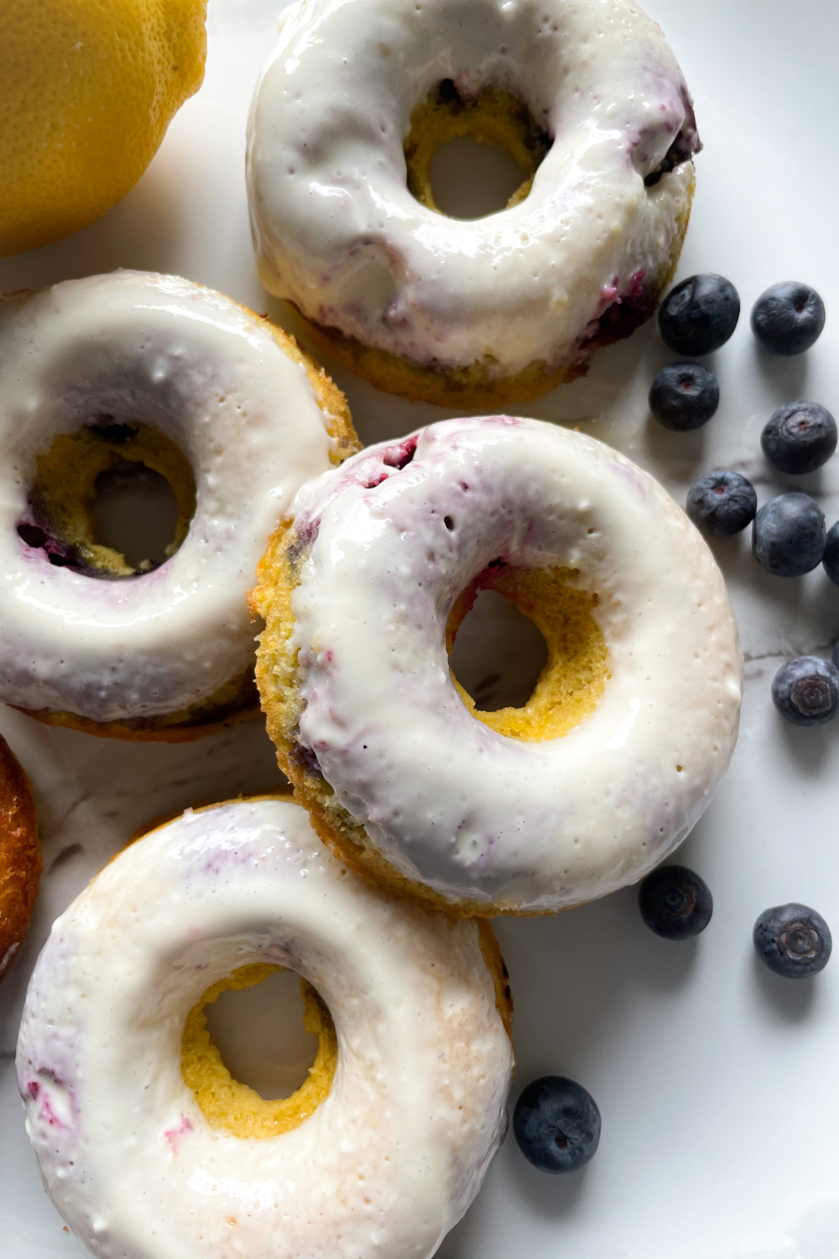 donuts on marble plate with blueberries and lemon