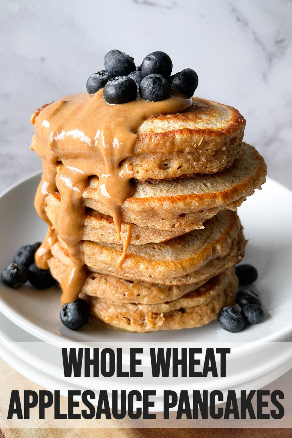 fluffy stacked whole wheat pancakes on plate with peanut butter and blueberries with text overlay