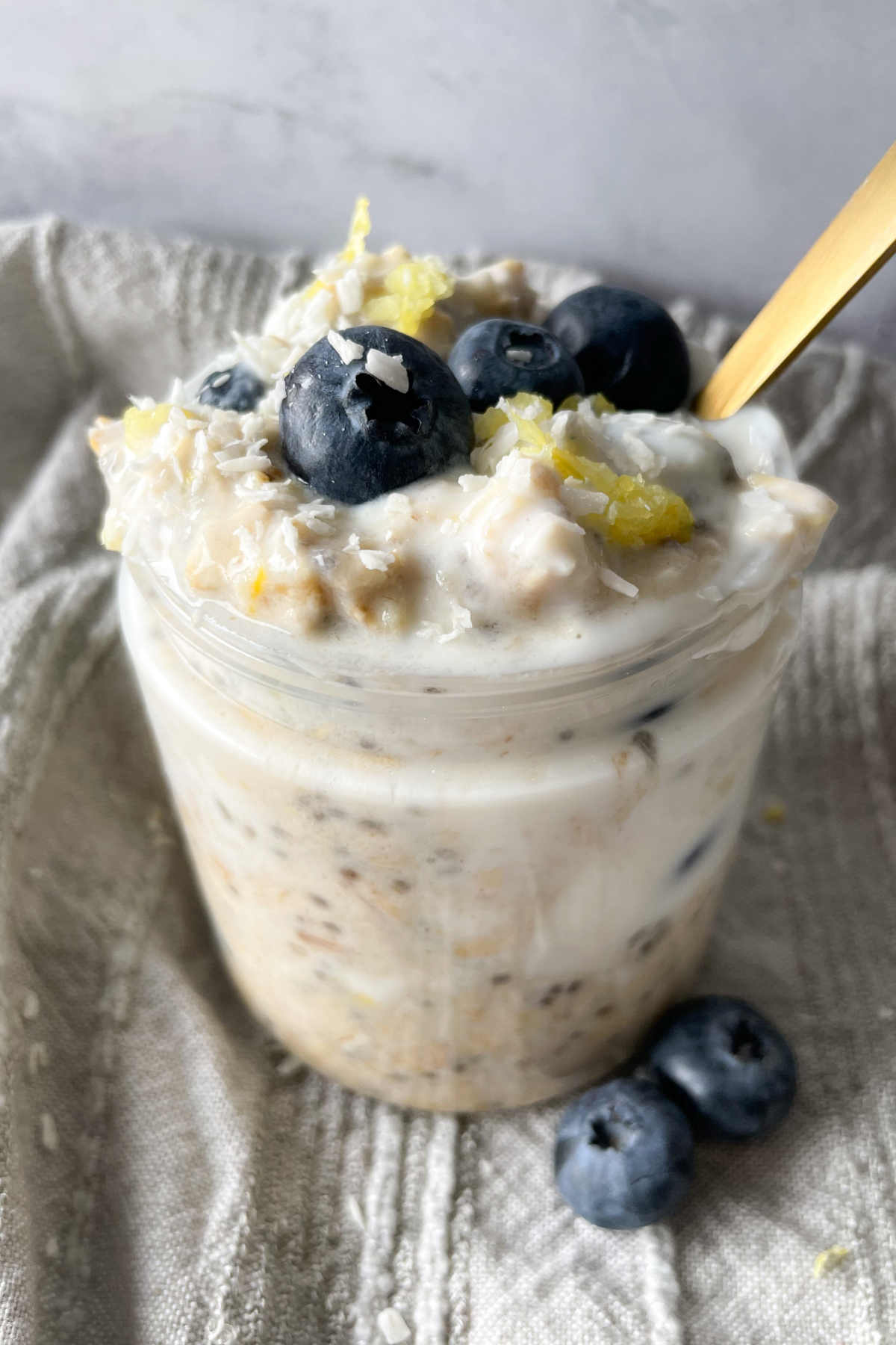 overnight oats in a jar with a grey napkin and gold spoon