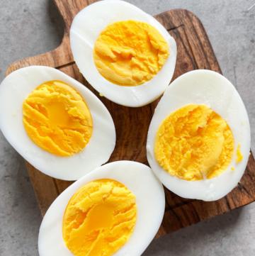 2 hard boiled eggs cut open on wooden board