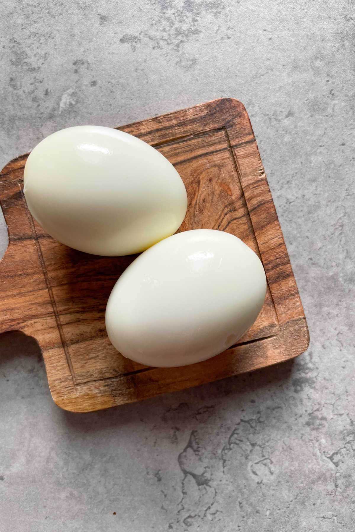 2 peeled eggs on wooden board