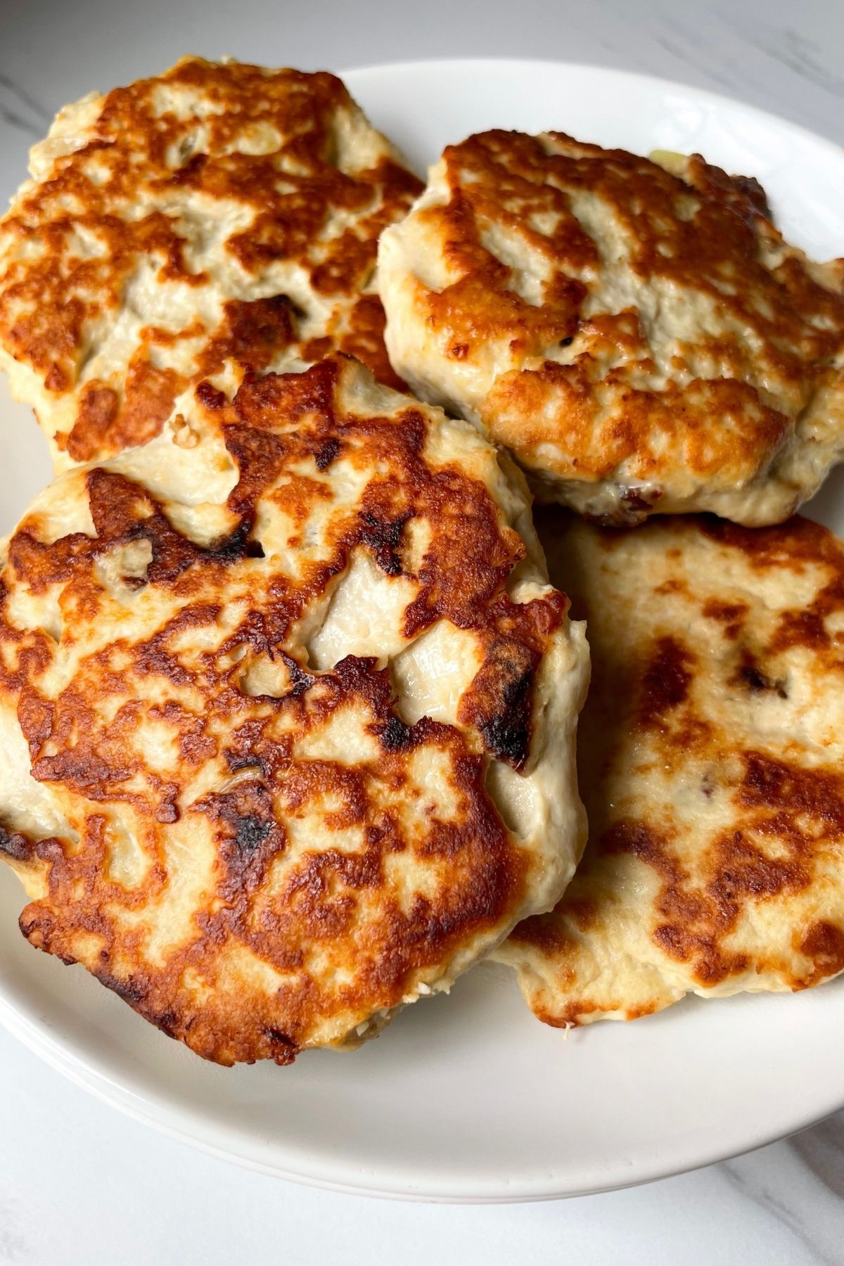 chicken burger patties on a white plate