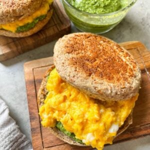 pesto egg breakfast sandwiches with pesto in the background