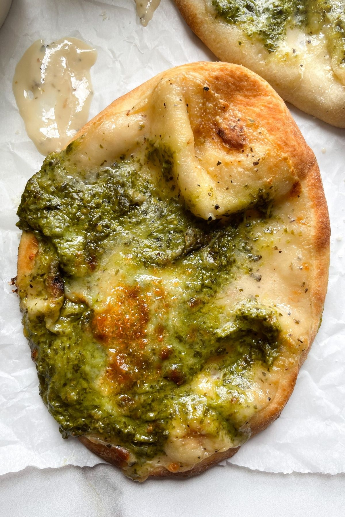 air fryer naan bread pizza on white parchment paper