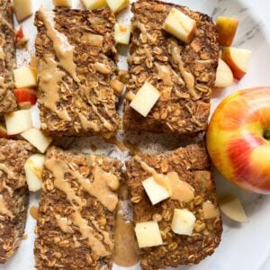 baked oatmeal bars on plate with apples