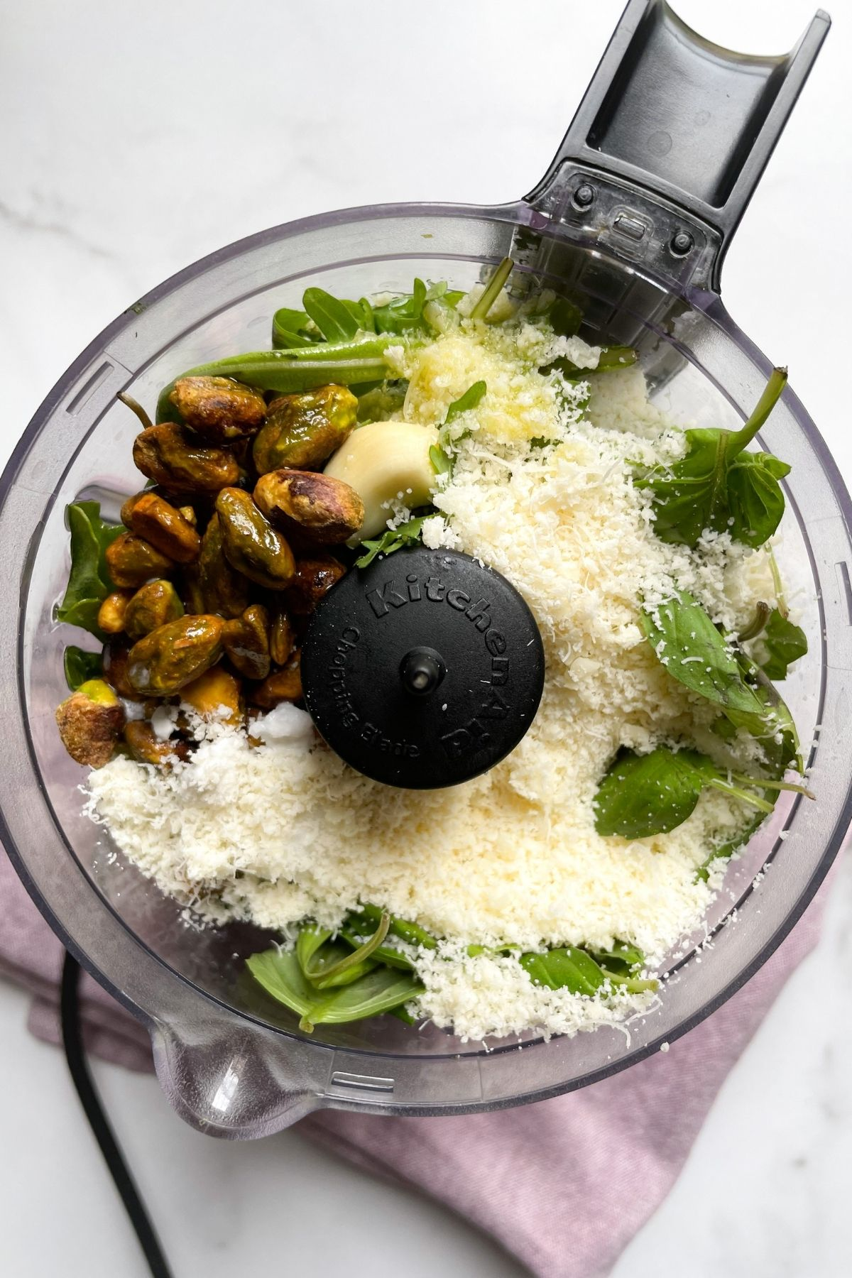 food processor with ingredients to make pesto