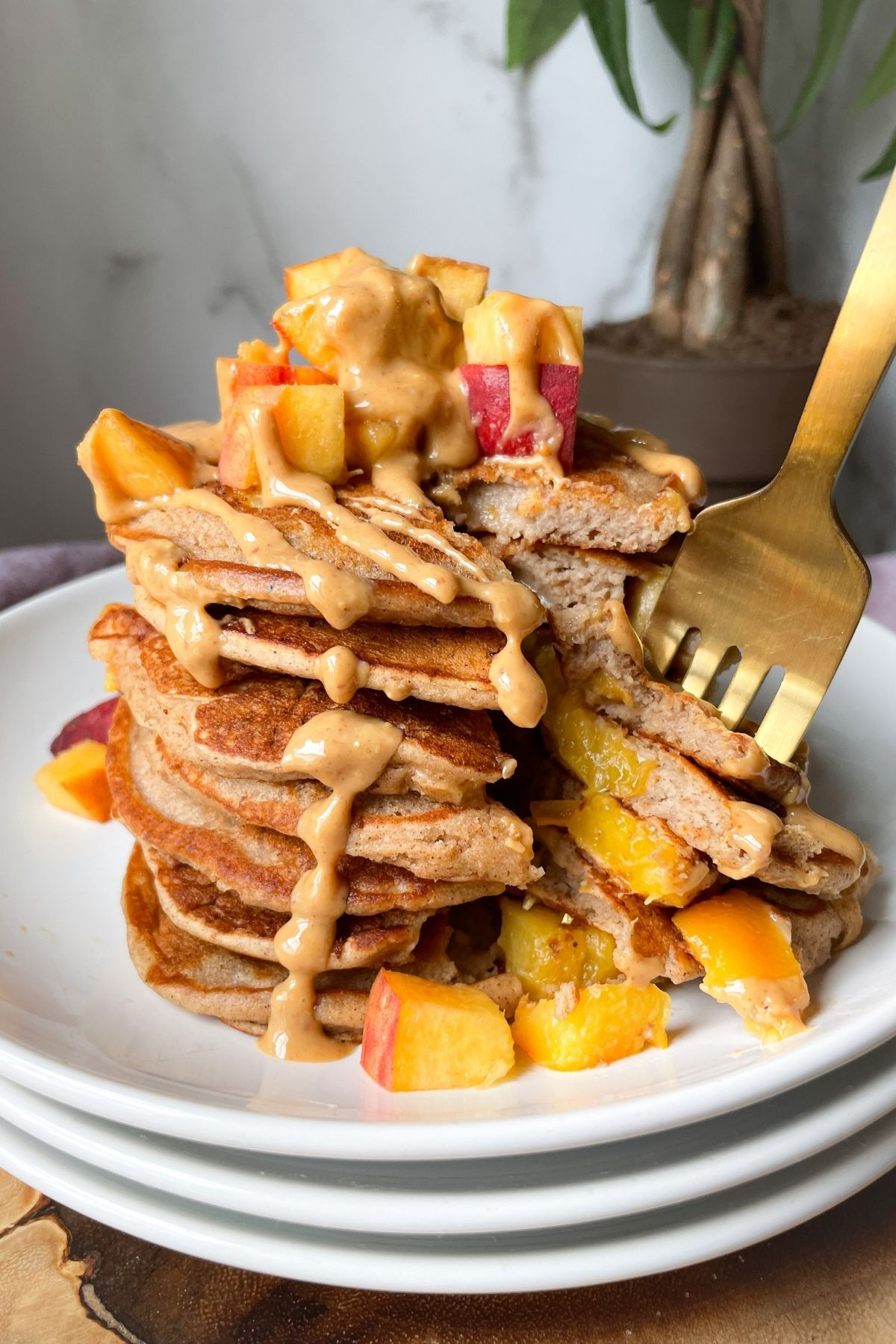 stacked peach pancakes on plates with gold fork