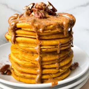 stacked pumpkin pancakes with almond butter and pecans