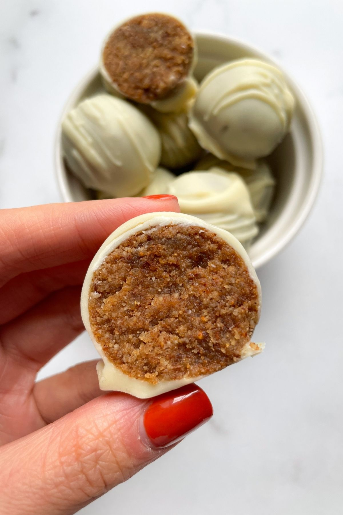 hand holding snickerdoodle cookie dough truffles with almond butter