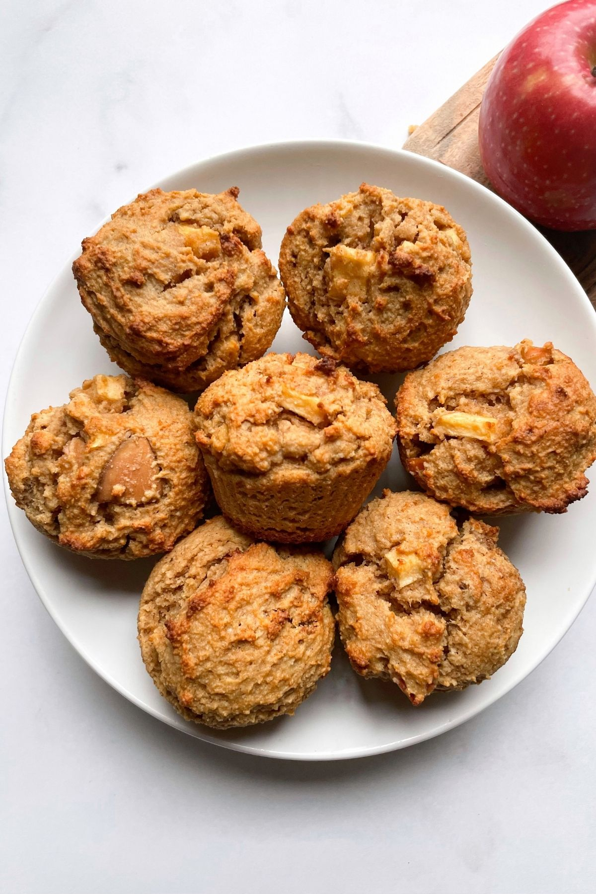 Healthy Peanut Butter Apple Muffins on plate with an apple in the background